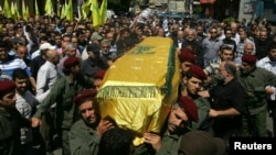 Supporters of Hezbollah and relatives of Hezbollah member Hussein Ahmad Abu Hasan carry his coffin during his funeral in Beirut's suburbs May 21, 2013.