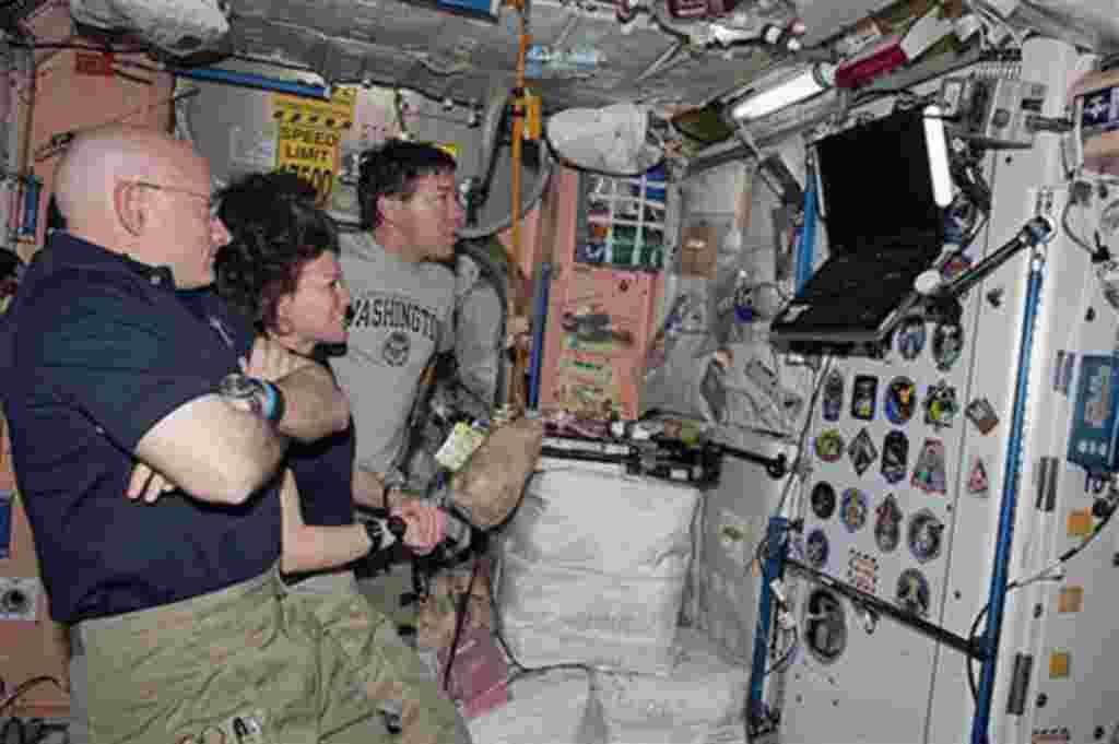 Los astronautas Scott Kelly, Cady Coleman y Michael Barratt observan el monitor del transbordador Discovery mientras este se aleja de la Estación Espacial Internacional.