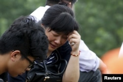 A relative of a passenger of the sunken cruise ship cries on a road to the site of the sinking in the Jianli section of Yangtze River, Hubei province, China, June 3, 2015.