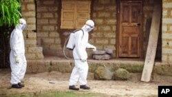 Des agents de la santé pulvérisent du désinfectant dans une parcelle dont un des habitants est suspecté d'être atteint du virus Ebola, à Freetown, Sierra Leone.