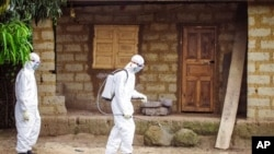 FILE - A healthcare worker in protective gear sprays disinfectant around the house of a person suspected to have the Ebola virus in Port Loko Community, situated on the outskirts of Freetown, Sierra Leone,Oct. 21, 2014.