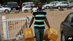 A man carries empty containers to buy fuel at a gas station in Abuja, Nigeria, May 26, 2015.