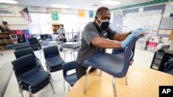 美國愛荷華州得梅因市的一名小學員工在給桌椅消毒。