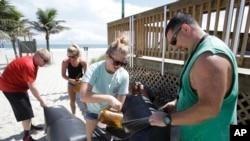 Kristen Allen (tengah, depan) dan Travis Scott (kanan) bersiap menghadapi badai Matthew dengan mengisi tas dengan pasir untuk mengantisipasi banjir agar tidak masuk ke toko suvenir di Cocoa Beach, Florida, 5 Oktober 2016. (AP Photo/John Raoux)