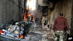A Syrian soldier, right, and citizens gather at an alley that was destroyed by two cars bombs, at Jaramana neighborhood, in the suburb of Damascus, Syria, Wednesday, Nov. 28, 2012. (AP Photo/SANA)
