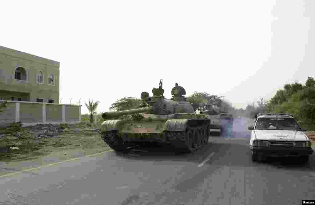 Army tanks drive on a street in the southern Yemeni city of Zinjibar, June 12, 2012.