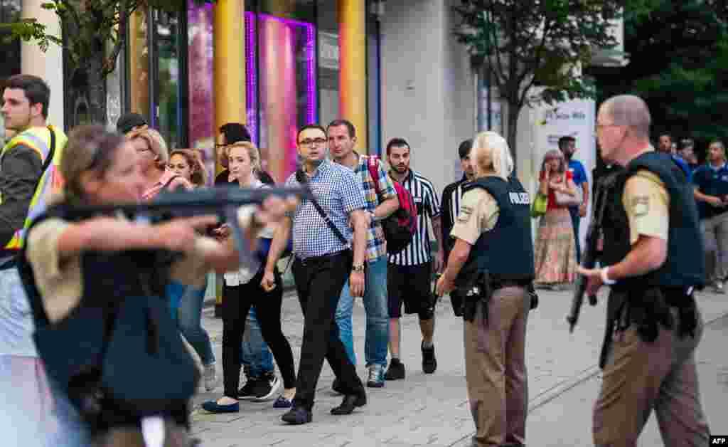 پولیس اہلکار فائرنگ کے بعد لوگوں کو شاپنگ سینٹر سے باہر نکالتے ہوئے