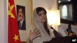 Pakistan's Foreign Minister Hina Rabbani Khar speaks near a portrait of Pakistan's Prime Minister Yusuf Raza Gilani at the Pakistan Embassy in Beijing, China, August 24, 2011