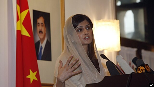 Pakistan's Foreign Minister Hina Rabbani Khar speaks near a portrait of Pakistan's Prime Minister Yusuf Raza Gilani at the Pakistan Embassy in Beijing, China, August 24, 2011