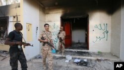 Libijske snage ispred zgrade američkog konzulata u Bengaziju, oštećene u požaru, 14. septembar 2012.