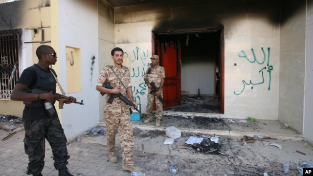 Libyan military guards check one of the U.S. Consulate's burnt out buildings during a visit by Libyan President Mohammed el-Megarif, not shown, to the U.S. Consulate, Sept 14, 2012.