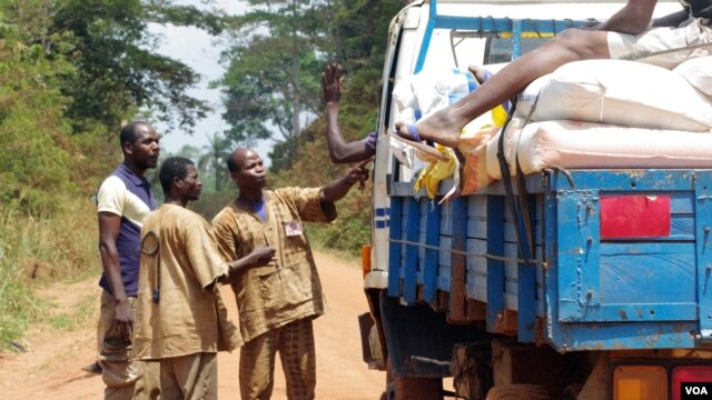 Traditional hunters known as dozos accost a truck driver at an illegal checkpoint north of the western Ivory Coast town of Duekoue, February 15, 2013. (Robbie Corey-Boulet for VOA)