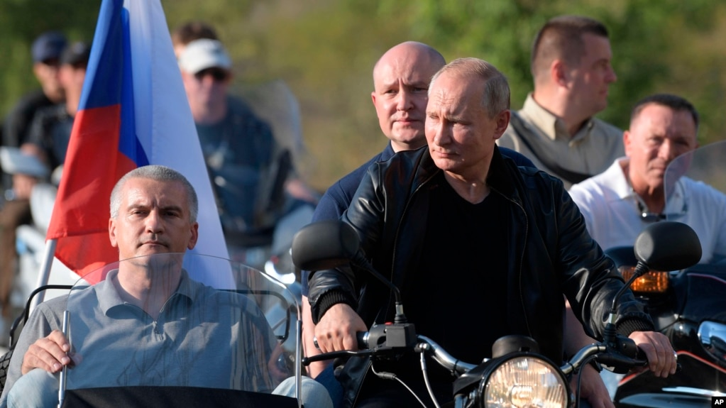 Russian President Vladimir Putin drives a motorbike during the Babylon's Shadow bike show camp near in Sevastopol, Crimea, Saturday, Aug. 10, 2019. Head of the Republic of Crimea Sergei Aksenov, is in sidecar, and acting Governor of Sevastopol…