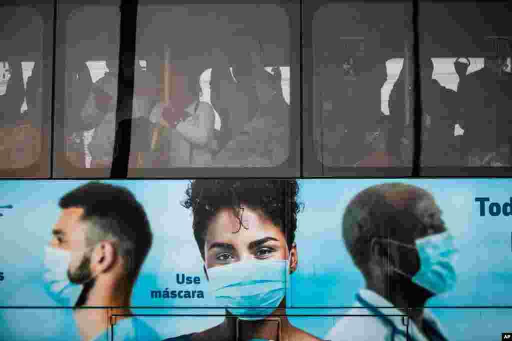 브라질 리오데자네이루 시민들이 탄 버스에 신종 코로나바이러스 방역 지침인 마스크 쓰기 캠페인 사진이 덮여 있다.