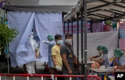 Muaythai boxing fighters and officials gather at a makeshift screening facility as a man in a Hazmat suite talks with a nurse outside Rajadamnern boxing stadium in Bangkok, Thailand, Thursday, March 19, 2020.