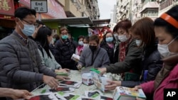 People buy face masks from a street vendor in Hong Kong, Saturday, Feb, 1, 2020.