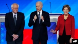 Democratic presidential candidates from left, Sen. Bernie Sanders, I-Vt., former Vice President Joe Biden and Sen. Elizabeth Warren, D-Mass., stand on stage Friday, Feb. 7, 2020, before the start of a Democratic presidential primary debate hosted by…