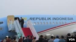Presiden Joko Widodo di atas tangga pesawat kepresidenan di Bandara Halim Perdana Kusuma (24/10). (VOA/Andylala Waluyo)