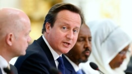 Britain's Prime Minister David Cameron speaks as Britain's Foreign Secretary William Hague, left, and Somali President Hassan Sheikh  Mohamud listen at the Somalia conference in London, May 7, 2013.