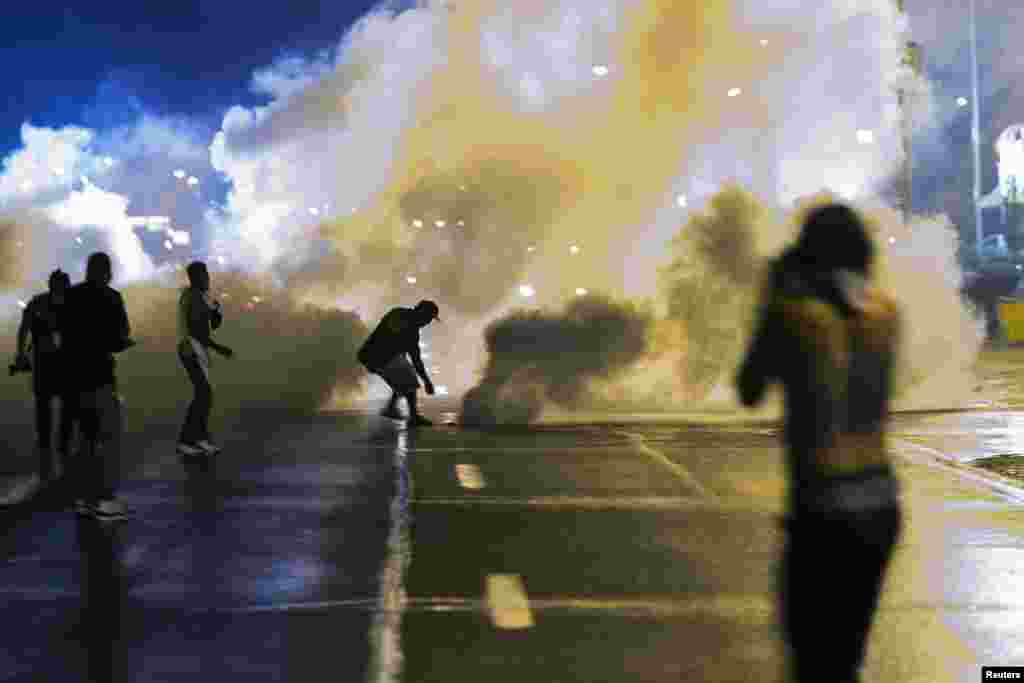 A protester reaches down to throw back a smoke canister as police clear a street after the passing of a midnight curfew meant to stem ongoing demonstrations in reaction to the shooting of Michael Brown in Ferguson, Missouri, USA.