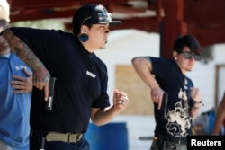FILE - Damien Chee (L) and Skylar Simon practice drawing their weapon during a firearms training class attended by members of the Pink Pistols, a national pro-gun LGBT organization, at the PMAA Gun Range in Salt Lake City, Utah, July 1, 2016.