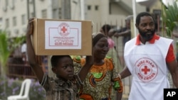 FILE - A child with his mother from Makoko slum carries their food parcel distributed by the Nigerian Red Cross, provided for those under coronavirus-related movement restrictions, in Lagos, Nigeria, April 25, 2020.