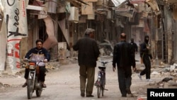 Seorang pria mengendarai sepeda motornya melewati warga dan para pejuang pembebasan Suriah yang berjalan kaki di sebuah jalan di Deir al-Zor, 13 Maret 2013 (REUTERS/ Khalil Ashawi). Media pro-pemerintah Suriah, al-Watan, menuduh bahwa pejuang asing yang radikal telah bergabung dengan pemberontak yang berupaya menggulingkan Presiden Bashar al-Asaad dalam dua tahun belakangan (17/3).