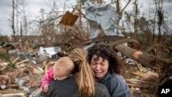Carol Dean, (derecha) llora mientras es abrazada por Megan Anderson y su hija de 18 meses, Madilyn, mientras Dean busca entre los escombros de la casa que compartía su esposo, David Wayne Dean, quien murió cuando un tornado azotó Beauregard, Alabama, el 3 de marzo de 2019.
