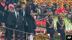 El presidente Barack Obama y el primer ministro indio, Narendra Modi, saludan a la multitud a su llegada al desfile.