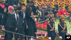 U.S. President Barack Obama, Indian Prime Minister Narendra Modi, left, and President Pranab Mukherjee wave to the crowd at the end of India's annual Republic Day parade in New Delhi, India, Monday, Jan. 26, 2015. (AP Photo/Manish Swarup)