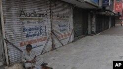 Một người bàn hàng rong ở Karachi ngồi cạnh dãy cửa hàng đóng cửa vì tình trạng bạo động trong thành phố