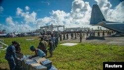 美军士兵和菲律宾民众11月17日在菲律宾灾区卸下救援物资。