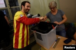A man, wearing a shirt with the colors of Catalan regional flag, casts his vote in a polling station of the banned separatist referendum in Barcelona, Spain, Oct. 1, 2017.