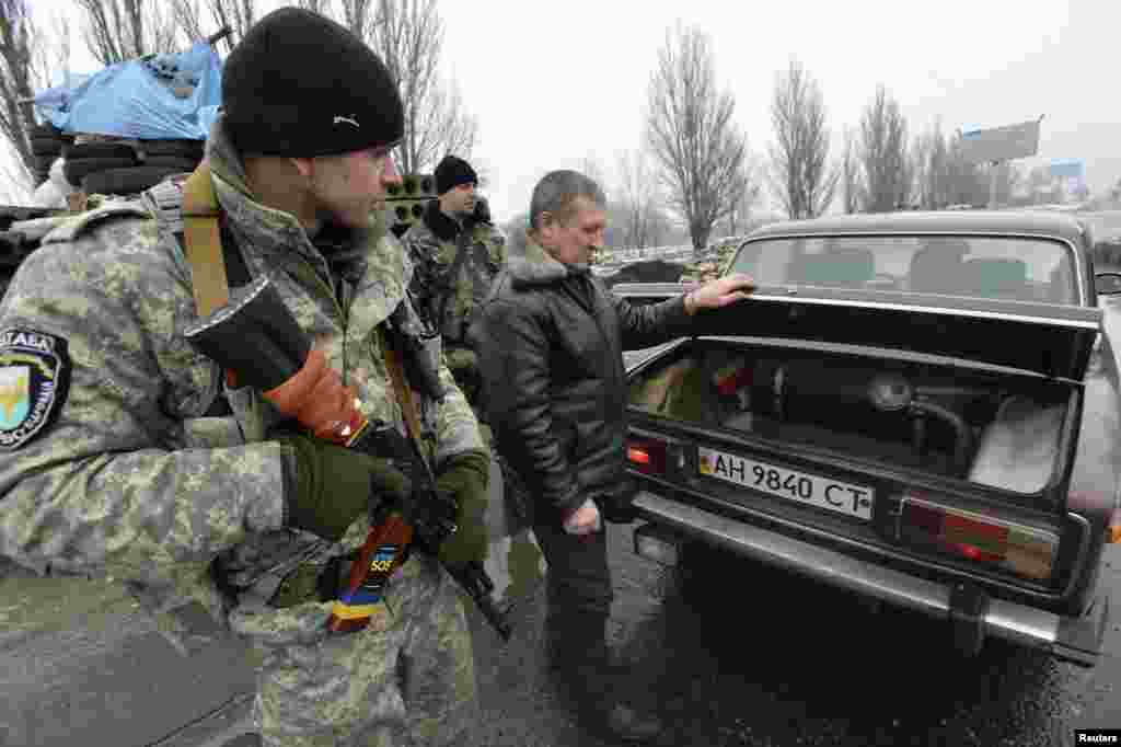 Members of the Ukrainian armed forces inspect a car at a checkpoint on the outskirts of Kostyantynivka, in the Donetsk region of Ukraine, Jan. 22, 2015.