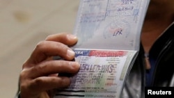 FILE - A foreign national shows a canceled U.S. visa in his passport, having been denied entry, at Washington Dulles International Airport in Chantilly, Virginia, Feb. 6, 2017.