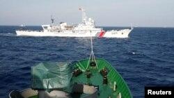 资料照:一艘越南海岸警卫队的船只在南中国海上看着一艘中国海岸警卫队的船只。
