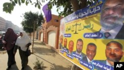 埃及婦女11月28日在埃及穆斯林兄弟會的選舉海報前步過。