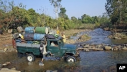 A man leaps onto a truck as it forges a creek in a rural part of Burma's Kachin state, February 26, 2012.