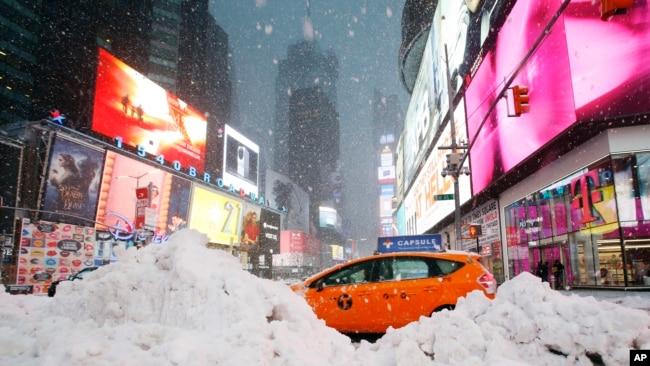 Un taxista pasa entre una montaña de nieve acumulada en Time Square, en la ciudad de Nueva York, el martes, 14 de marzo, de 2017.