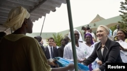 U.S. Secretary of State Hillary Clinton (R) gives a mosquito net for malaria prevention to a local woman during a tour of the Philippe Senghor Health Center in Dakar, Senegal, August 1, 2012.