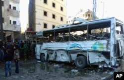 In this photo released by the Syrian official news agency SANA, Syrians gather where three bombs exploded in Sayyda Zeinab, a predominantly Shiite Muslim suburb of the Syrian capital, Syria, Jan. 31, 2016.