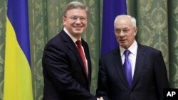 European Commissioner for Enlargement and European Neighborhood Policy Stefan Fuele, left, shakes hands with Ukraine Prime Minister Mykola Azarov during their meeting in Kiev, Ukraine, February 7, 2013.