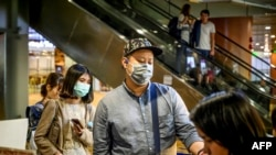 Passengers wearing face masks board their flight at Yangon International Airport on January 21, 2020. - China has confirmed human-to-human transmission in the outbreak of a new SARS-like virus as the number of cases soared and authorities January 21 said