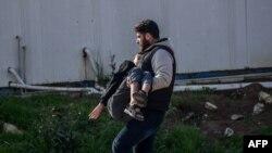 31일 로켓 공격이 발생한 터키-시리아 접경 하타이주레이한리 지역에서 한 남성이 부상자를 안고 걸어가고 있다.