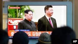 FILE- People watch a TV screen showing file footage of North Korean leader Kim Jong Un and Chinese President Xi Jinping, right, during a news program at the Seoul Railway Station in Seoul, South Korea, Jan. 8, 2019.