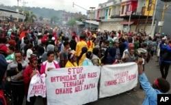 "Para pengunjuk rasa membawa spanduk-spanduk bertuliskan ""Stop intimidasi dan rasismen terhadap orang Asli Papua"" dalam unjuk rasa di Manokwari, Provinsi Papua, 19 Agustus 2019."