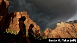 Hikers look up at a fast moving storm as it makes its way through Zion National Park outside of Springdale, Utah.