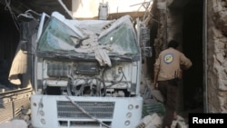 FILE - A civil defense member inspects the damage after the agency's center was hit by an airstrike in a rebel-held area of Aleppo, Syria, Aug. 12, 2016.