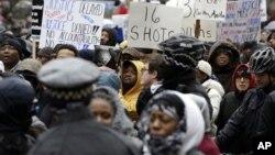 抗议者走到芝加哥市的北密西根大道,参加社区活动人士和劳工领袖组织的示威活动。(2015年11月27日)