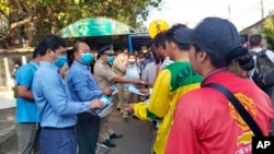 FILE: In this Jan. 27, 2020, photo provided by the Poipet International Checkpoint, government officials distribute face masks to tourists during a launch of a plan to distribute a million masks to travelers arriving at the checkpoint with Thailand as a safety precaution against